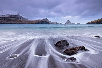 Waves crash onto the black sandy beach at Bour on the island of Vagar in the Faroe Islands, Denmark, Europe - p871m1048039 by Adam Burton
