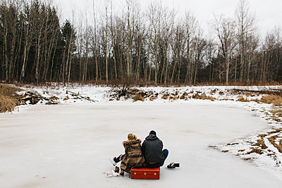 Couple sitting on red suitcase in middle of frozen lake, Whitby, Ontario, Canada - p924m1224822 by Jennifer van Son