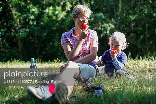 Mutter und Sohn sitzen auf einer Wiese und essen Tomaten, Haide, Ummanz, Insel Rügen, Mecklenburg-Vorpommern, Deutschland - p1316m1160577 von Roetting+Pollex