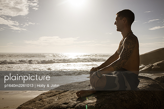 Man practises meditation on the beach at sunset - p1640m2261013 by Holly & John