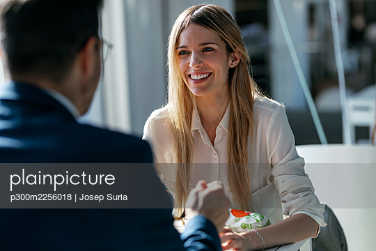 Smiling businesswoman having lunch with colleague while sitting in cafeteria at office - p300m2256018 by Josep Suria