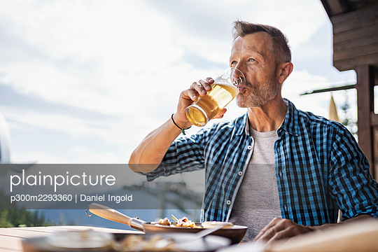 Man drinking beer while sitting at restaurant - p300m2293360 by Daniel Ingold