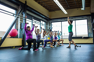 Fitness instructor guiding women in lifting dumbbells at gym - p1166m1417404 by Cavan Images