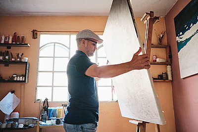 Mid adult man working as painter holding canvas on easel in his studio - p1166m2078305 by Cavan Images