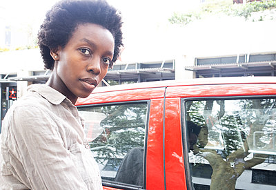 Young African woman is standing by the car - p1640m2260080 by Holly & John