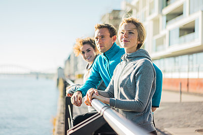 Friends leaning on railing at the riverside after training - p300m2070476 by Robijn Page