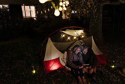 Senior couple with tablet camping in garden of their home at night - p300m2155273 by Gustafsson