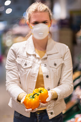 Teenage girl wearing protectice mask and gloves holding yellow bell peppers - p300m2225045 by Anke Scheibe