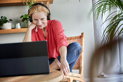 Woman with headphones doing video call on laptop at home - p300m2266066 by Jo Kirchherr