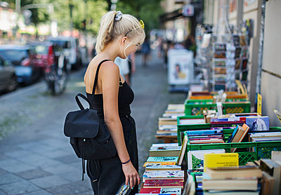 Young woman looking at books on stall - p312m2101690 by Pernille Tofte