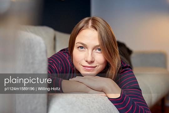 Junge Frau entspannt sich in ihrer Wohnung - p1124m1589196 von Willing-Holtz