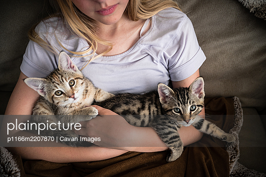 Young Girl In Lavender Shirt Holding Two Small Kittens in her Arms - p1166m2207870 by Cavan Images