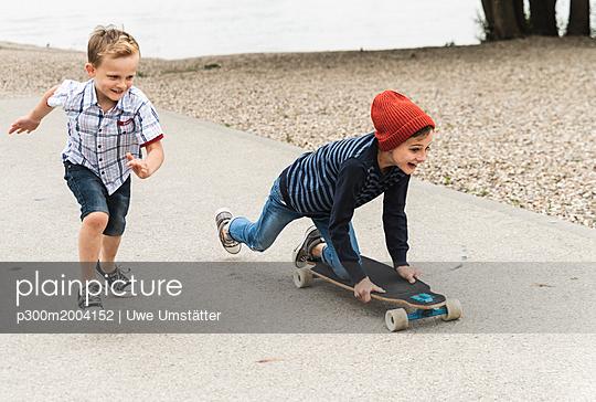 Happy boy running next to brother on skateboard - p300m2004152 von Uwe Umstätter