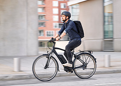 Bicycle courier riding an electric bike - p1124m2052993 by Willing-Holtz