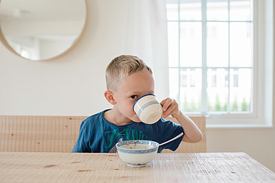 portrait of a young boy looking with one eye drinking at breakfast - p1166m2113239 by Cavan Images