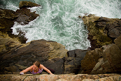 A young woman climbs to the top of a cliff with waves crashing below. - p1424m1501293 by Noah Couser