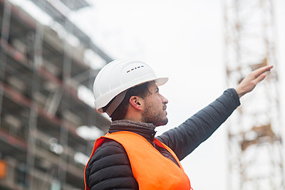 Man with wearing safety vest and hard hat at construction site - p300m1562930 by Sigrid Gombert