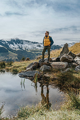 Mature man standing on rock by pond at Salzburger Land, Leogang Mountains, Austria - p300m2267365 by Mareen Fischinger