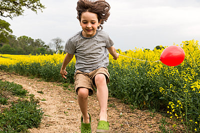 Boy jumping on yellow flower field track pulling red balloon - p429m1156039 by Bonfanti Diego
