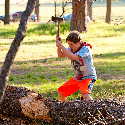 Caucasian boy chopping log with axe - p555m1532496 by Stephen Simpson Inc