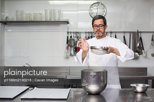 Chef sifting flour into bowl - p1166m2130218 by Cavan Images