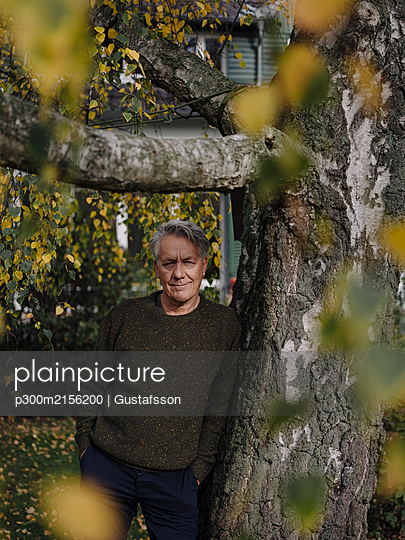 Portrait of a senior man at tree in garden - p300m2156200 by Gustafsson