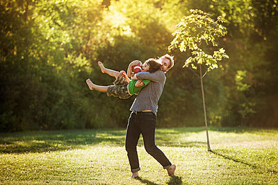 Father carrying boy while playing rugby in lawn - p1166m1098871f by Cavan Images