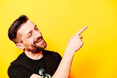 Man in front of a yellow background pointing with his pointing finger, portrait - p1267m2272513 by Jörg Meier