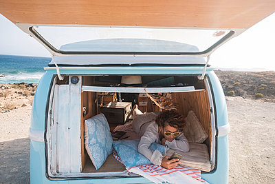 Spain, Tenerife, woman with cell phone lying in van parked at seaside - p300m1505918 by Simona Pilolla