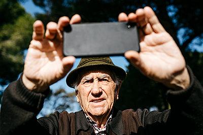 Spain, Barcelona. Retired senior man taking photos with his smartphone in a park - p300m2167188 von Josep Rovirosa