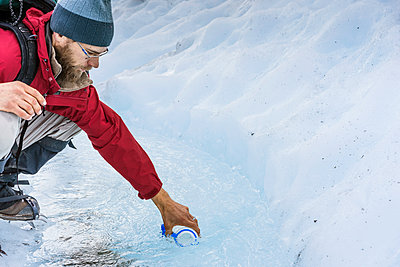 Male hiker collects water from glacial stream on Glacier Wrangell - p343m1475641 by Cavan Images