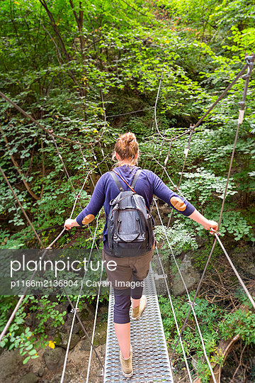 Hiker crossing metal suspension bridge on hiking trail. - p1166m2136804 by Cavan Images