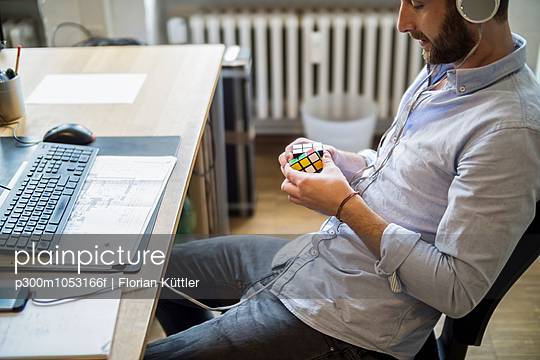 Young man in office at desk with Rubik\'s cube