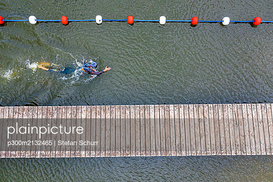Aerial view of a triathlete crawling in a lake - p300m2132465 by Stefan Schurr