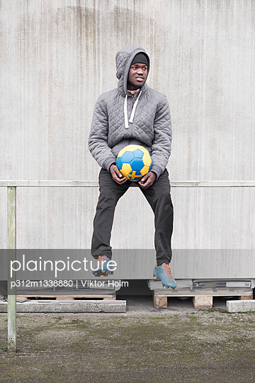 Man sitting with soccer ball