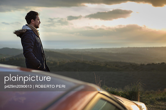 Man resting against car on roadside, enjoying view on hilltop - p429m2090613 by ROBERTO PERI