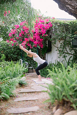 Blond woman doing yoga in a garden. - p1100m1080228 by Mint Images