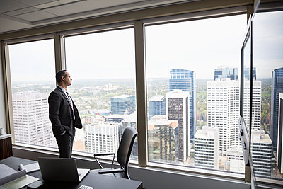 Pensive businessman looking out over city from conference room window - p1192m1183752 by Hero Images