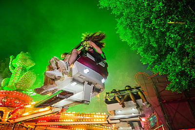 People in a fairground ride on a funfair at night - p300m2132145 by DREAMSTOCK1982