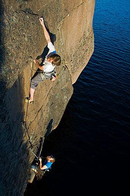 Two men climbing cliff above lake - p575m1074561f by Fredrik Schlyter
