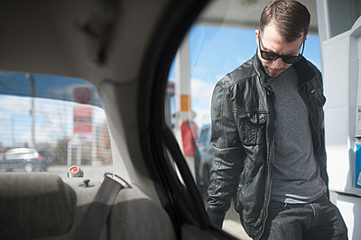 Young man putting fuel in car;  view from vehicle interior - p924m836526f by Hugh Whitaker