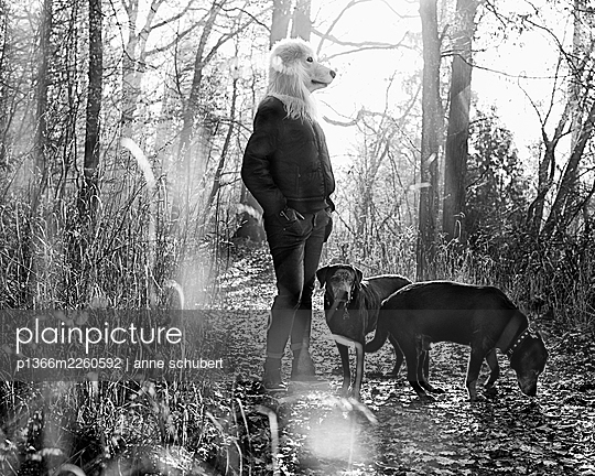 Woman with dog mask walks the dogs in a forest - p1366m2260592 by anne schubert