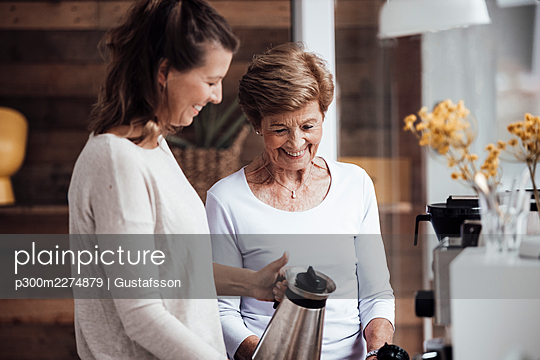 Smiling young woman holding kettle by grandmother at home - p300m2274879 by Gustafsson