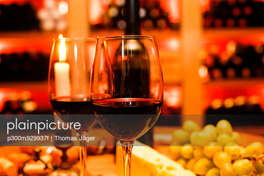 Two glasses of red wine, lightes candle, grapes and bottle in private wine cellar