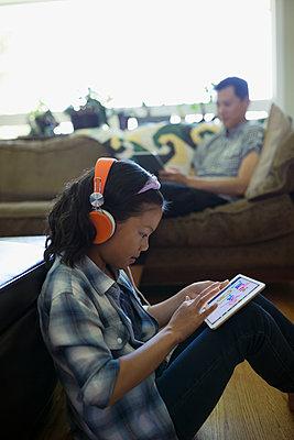 Girl with headphones using digital tablet in living room - p1192m1157988 by Hero Images