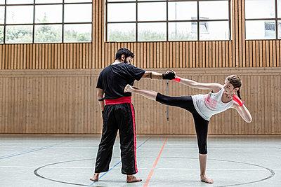 Female kickboxer sparring with coach in sports hall - p300m2144499 von Stefanie Baum