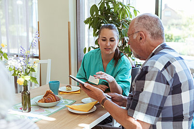 Young nurse and senior man using digital tablet at breakfast table in nursing home - p426m2072593 by Kentaroo Tryman