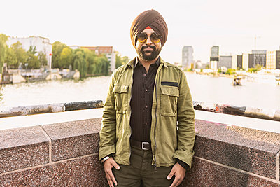 Indian man exploring city, river in background, Berlin, Germany - p429m2077807 by Tamboly