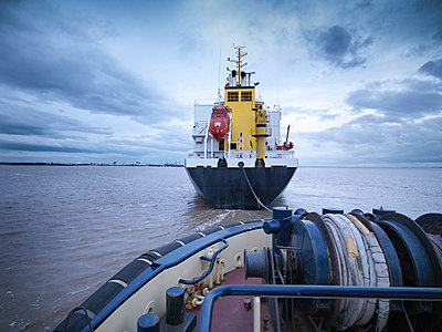 Tugboat towing ship out to sea - p429m747060f by Monty Rakusen