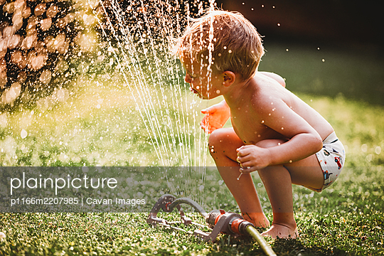 Child sticking tongue out drinking water from sprinkler in backyard - p1166m2207985 by Cavan Images